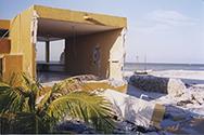 Photo of a yellow concrete building damaged by hurricane Isidore