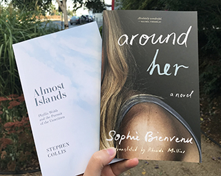 Photo of two books, Almost Islands and Around Her, taken in a parkette