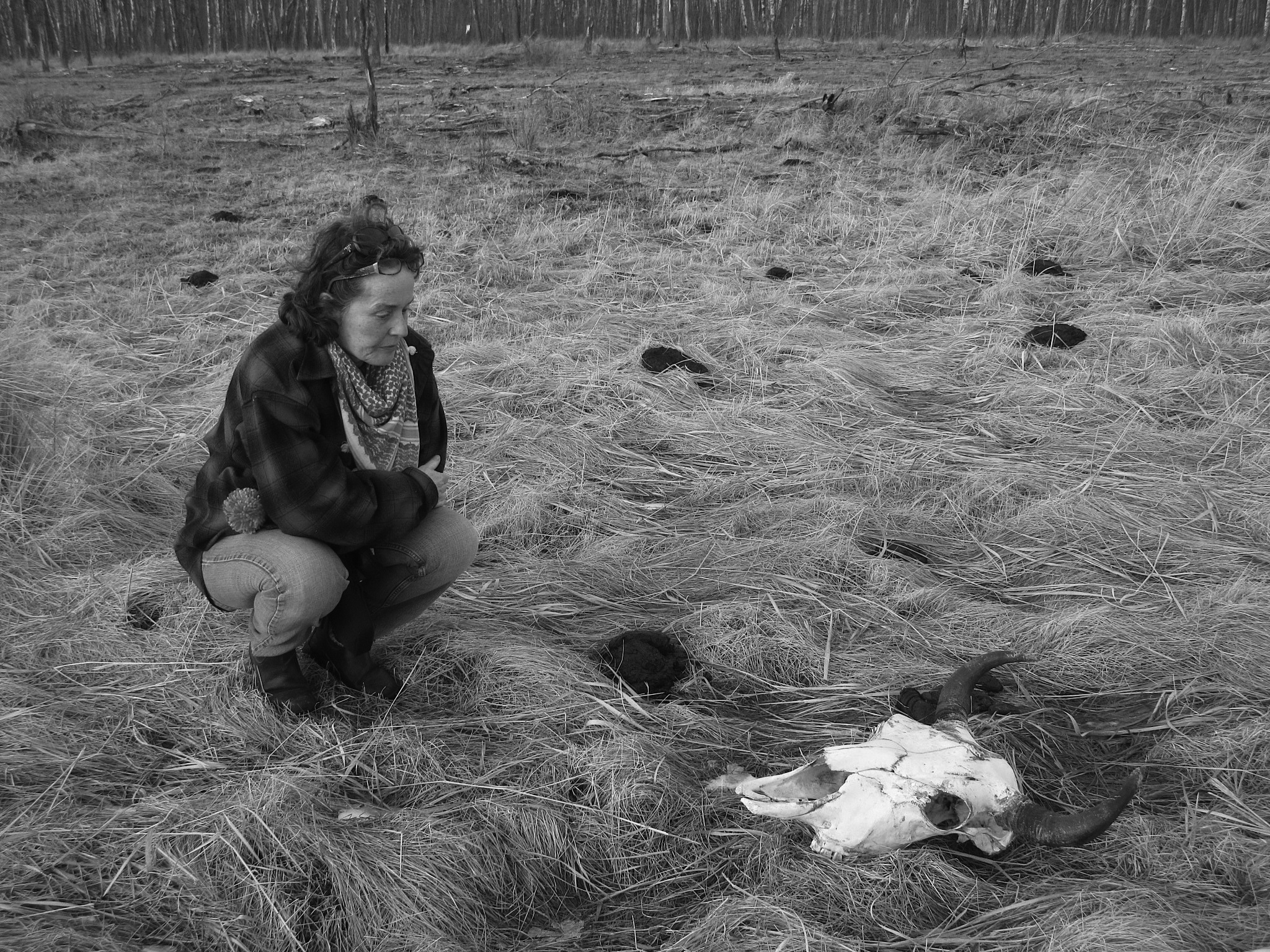 Christine Stewart crouches by a bison skull.