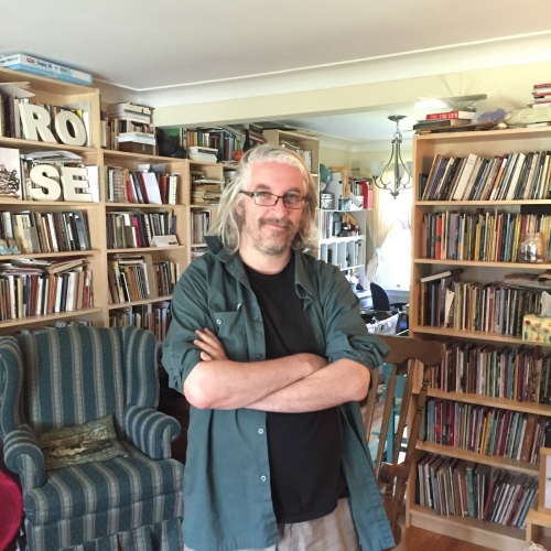 Photo of rob mclennan, in his home, surrounded by bookshelves.