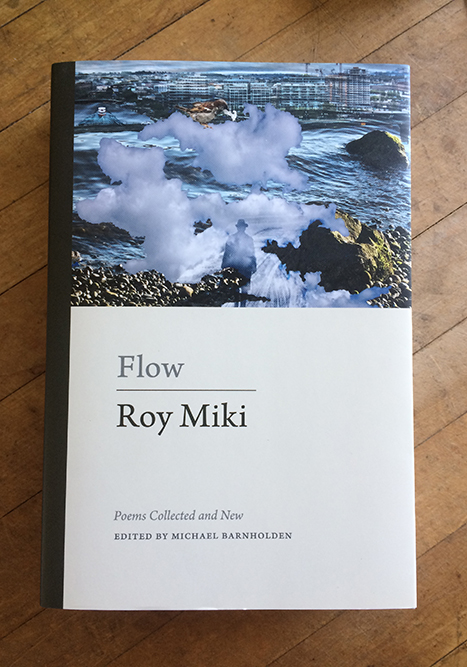 The softcover edition of Roy Miki's Flow on a wooden table in soft light.